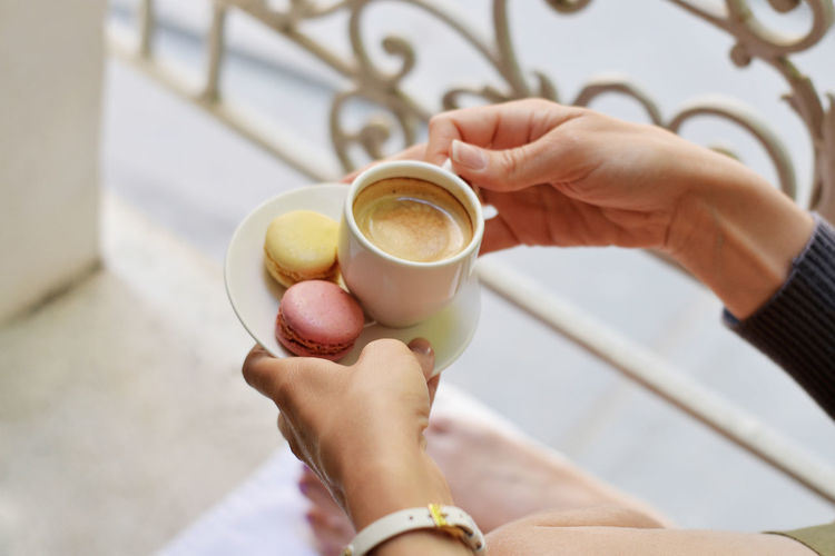 Cropped image of woman holding coffee cup with macaroons in saucer