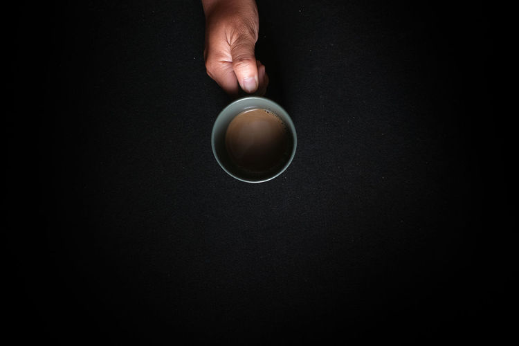 Directly above shot of hand holding coffee cup against black background