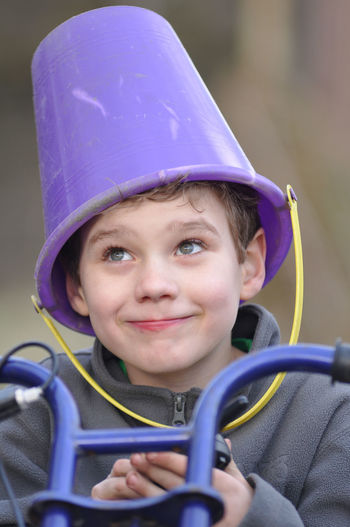 Close-up of boy with bucket on head riding bicycle