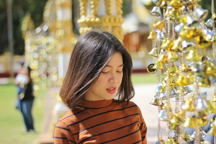 Close-up of woman with eyes closed standing by christmas decorations during sunny day
