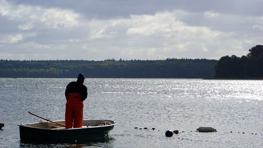 Man in boat on lake against sky