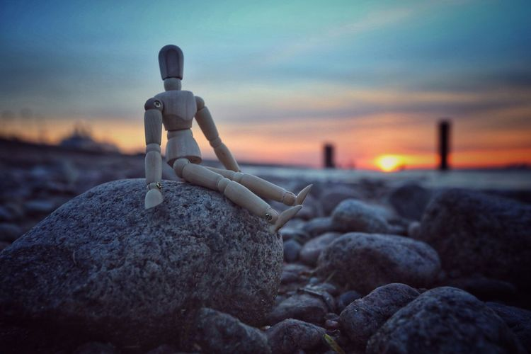 Close-up Of Wooden Figurine On Rock Against Sky During Sunset