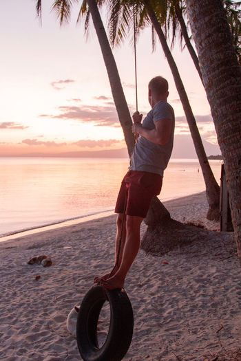 Full length of man swinging on tire swing at beach during sunset