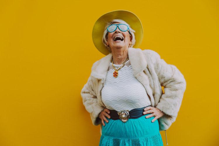 Cheerful senior woman standing against yellow background