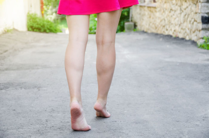 Girl in a red dress is walking barefoot along the road Adult Body Part Casual Clothing Child Day Dress Fashion Focus On Foreground Human Body Part Human Foot Human Leg Human Limb Limb Low Section One Person Outdoors Shoe Skirt Standing Teenager Women