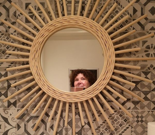 Woman taking selfie while reflecting on mirror