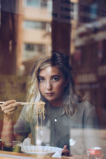 Portrait of young woman holding food in restaurant seen through glass window