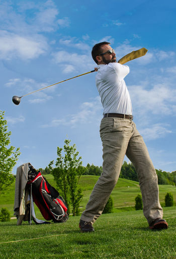 Business man swinging a golf club Blue Business Man Casual Clothing Cloud Cloud - Sky Day Enjoyment Field Full Length Fun Golf Grass Grassy Green Color Leisure Activity Lifestyles Man Nature Outdoors Playing Sky Sport Tree