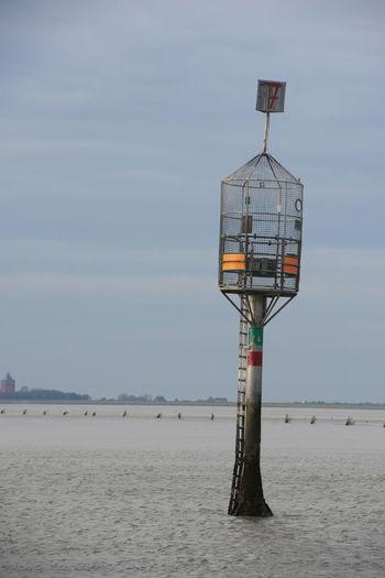 Lifeguard tower on beach against sky