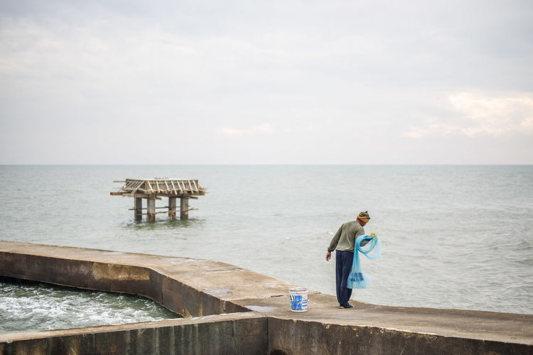 Beauty In Nature Casual Clothing Day Full Length Horizon Horizon Over Water Leisure Activity Lifestyles Looking At View Nature One Person Outdoors Real People Scenics - Nature Sea Side View Sky Standing Tranquility Water