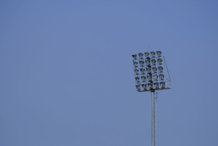 Low angle view of floodlight against clear blue sky