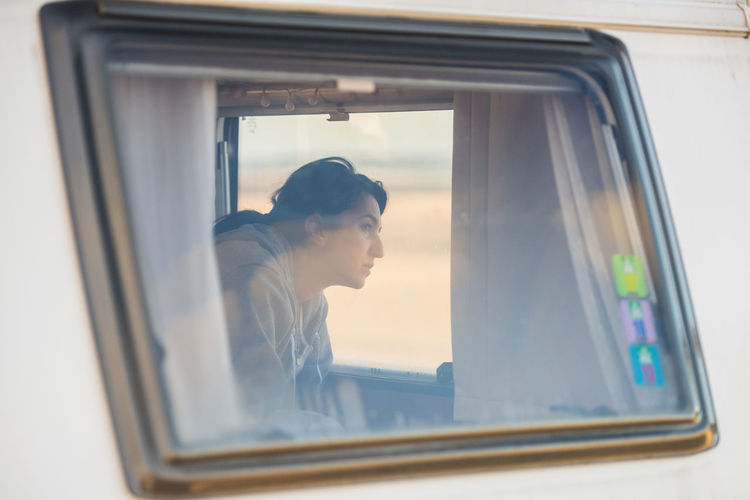 Woman In Camper Van Seen Through Window