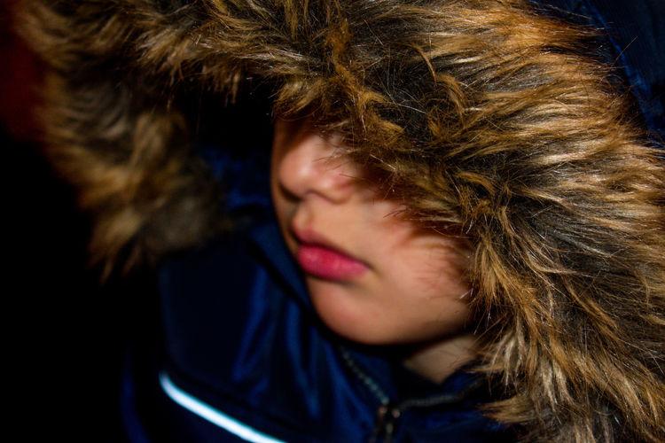 Close-up of boy wearing fur coat