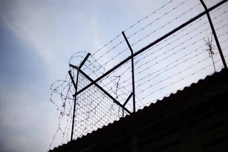 Low angle view of barbed wire fence against blue sky