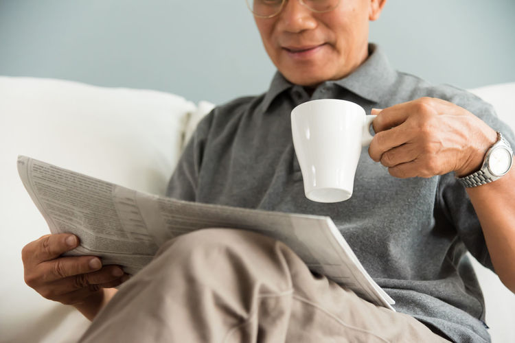 Midsection Of Smiling Senior Man With Tea Holding Newspaper While Sitting On Sofa