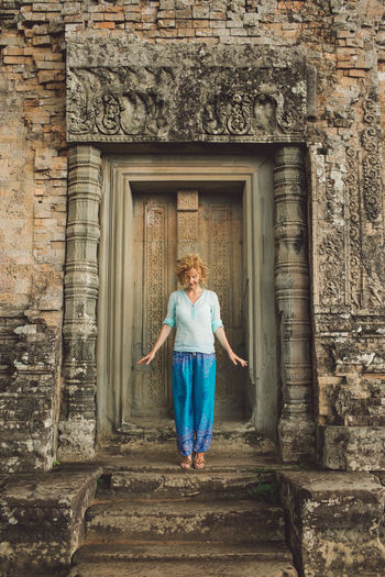 Smiling Mid Adult Woman Standing Outside Ankor Wat Temple