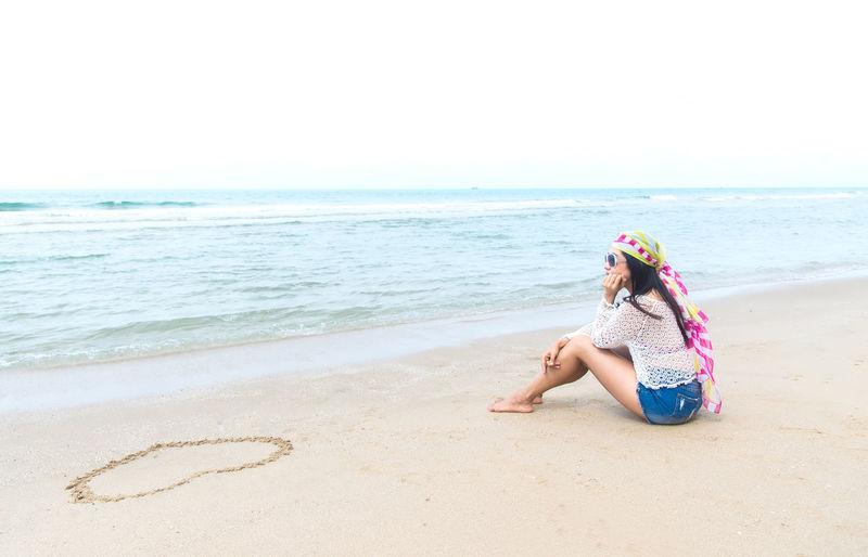 Woman sitting on beach by sea against sky