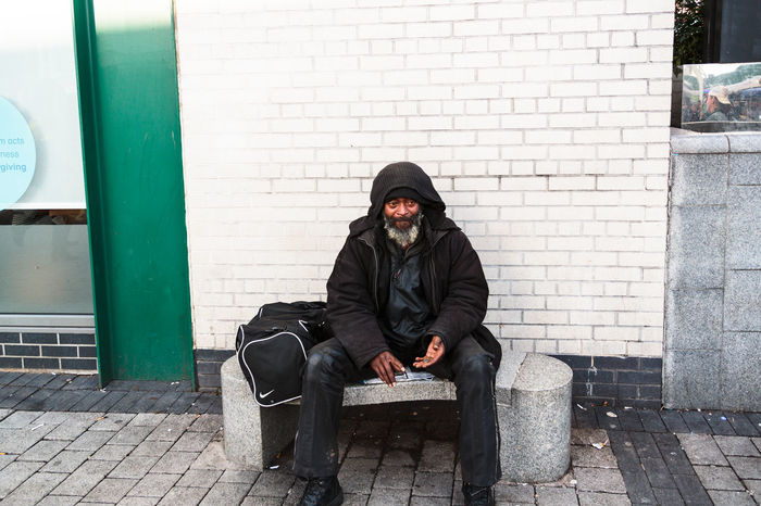 Older grey bearded black man in a heavy coat with the hood up sitting on a marble bench in the centre of Birmingham begging Adults Only Beard Bearded Begging Black Man City City Center Day Dirty Clothes Full Frame Homeless Horizontal Man No Filter Older Man One Man Only One Person Outdoors Real People Sitting Sitting Social Issues Street People Unedited Wide Angle