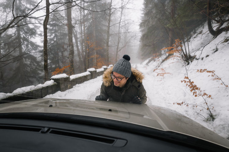 Man pushing car on snow covered road in forest
