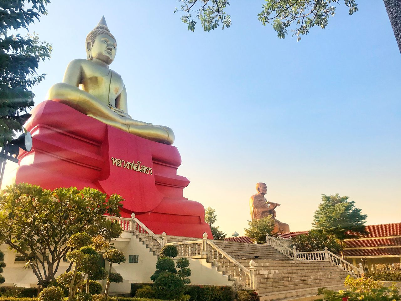 statue, sculpture, male likeness, human representation, religion, clear sky, low angle view, idol, tree, spirituality, no people, day, golden color, outdoors, sky