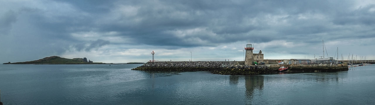 View of lighthouse by calm sea against cloudy sky