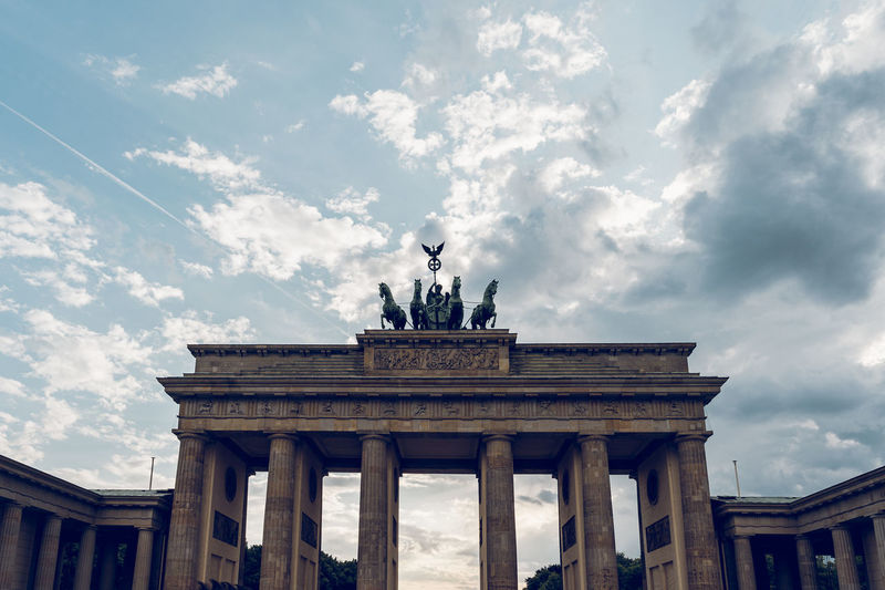 Low angle view of statue on brandenburg gate against cloudy sky
