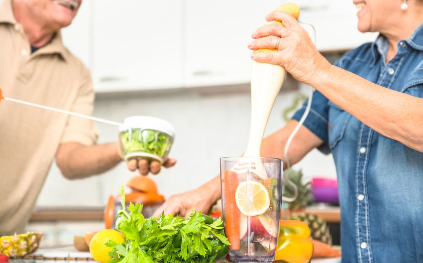 Midsection Of People Preparing Food On Table At Home