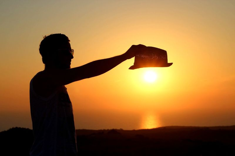 Silhouette man holding hat while standing against sky during sunset
