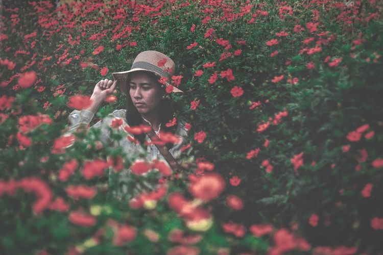Portrait of woman with red flowers in field