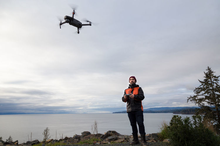 Full length of man operating drone