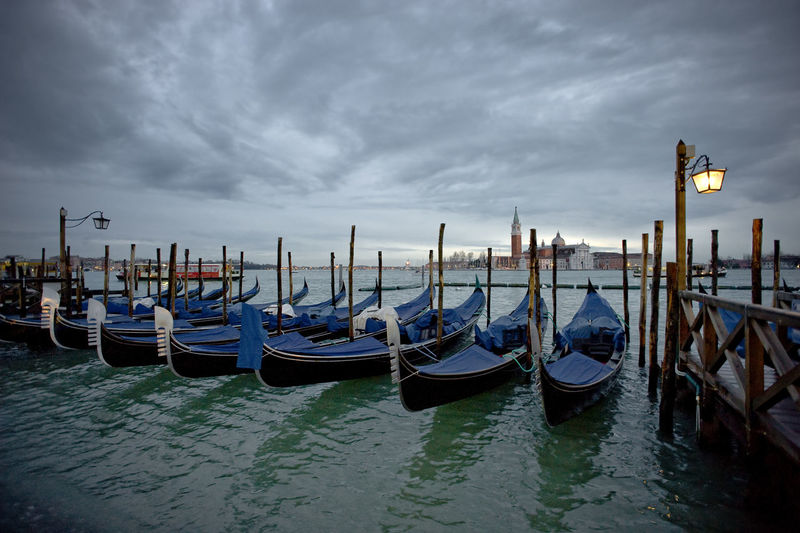 Gondolas Moored At Grand Canal By Santa Maria Della Salute Against Cloudy Sky