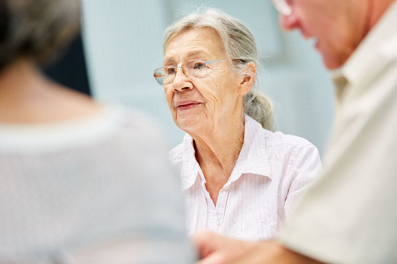 Thoughtful senior woman wearing eyeglasses while sitting with friends in nursing home