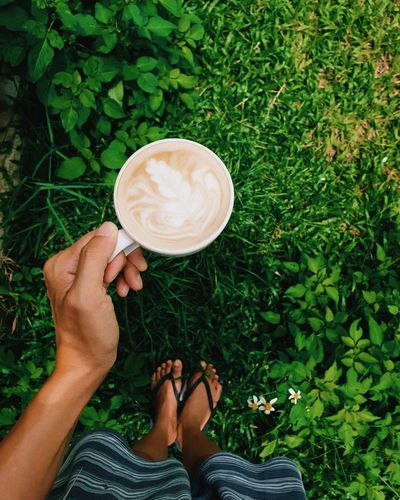Hand holding cup of coffee in garden at home. Cappuccino Mocha Cafe Macchiato Saucer Tea Black Coffee Espresso Coffee Cup Beverage Latte Coffee Foam Froth Art Personal Perspective Frothy Drink Low Section Growing Footwear Froth Blooming Human Leg Caffeine Shoe Matcha Tea Shoelace Coffee Pot Cafe Culture Cup Ground Coffee Human Foot