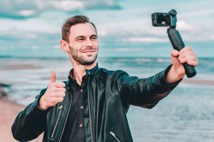 Man filming with video camera against sea