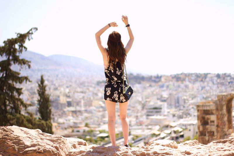 Rear view of young woman with arms raised standing on rock against cityscape