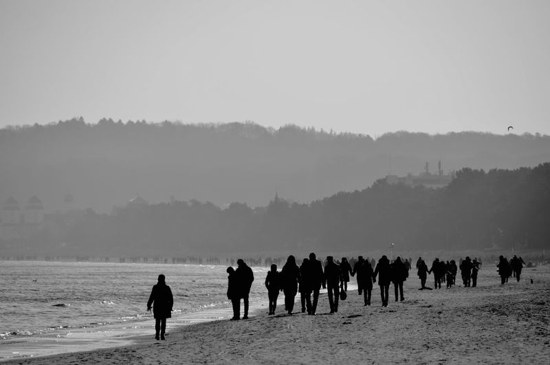 Silhouette people on shore against clear sky