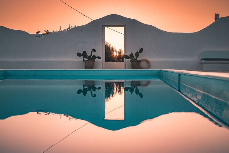 Teal&orange all weekend long✌️Mykonos Swimming Pool Water Sunset Reflection Clear Sky Mountain Outdoors No People Nature FollowMeOnInstagram Tealandorange Copy Space Travel Destinations Amazing View Vacations Traveling Greece ByThePool Holiday Holiday POV Day Sky Summer Summer Views Nopeople Connected By Travel