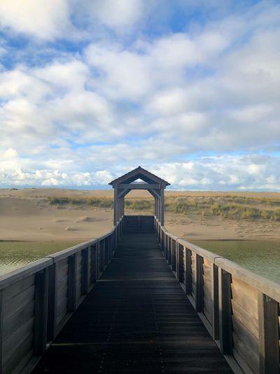 Wooden Bridge Over Water Against Sky