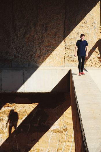 Full Length Shadow Sunlight One Person Real People Lifestyles Leisure Activity Day Walking Casual Clothing Young Men Men Young Adult Architecture Outdoors Built Structure Standing Mammal One Man Only People