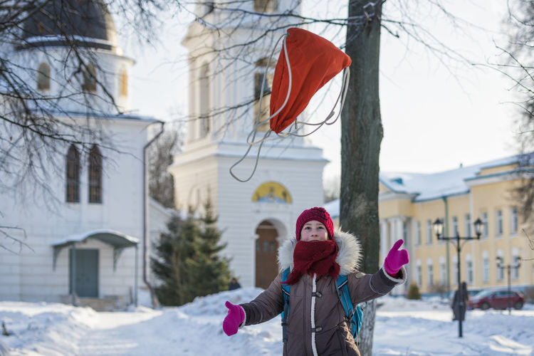 Girl Throwing Bag In Mid-Air While Standing In Snow