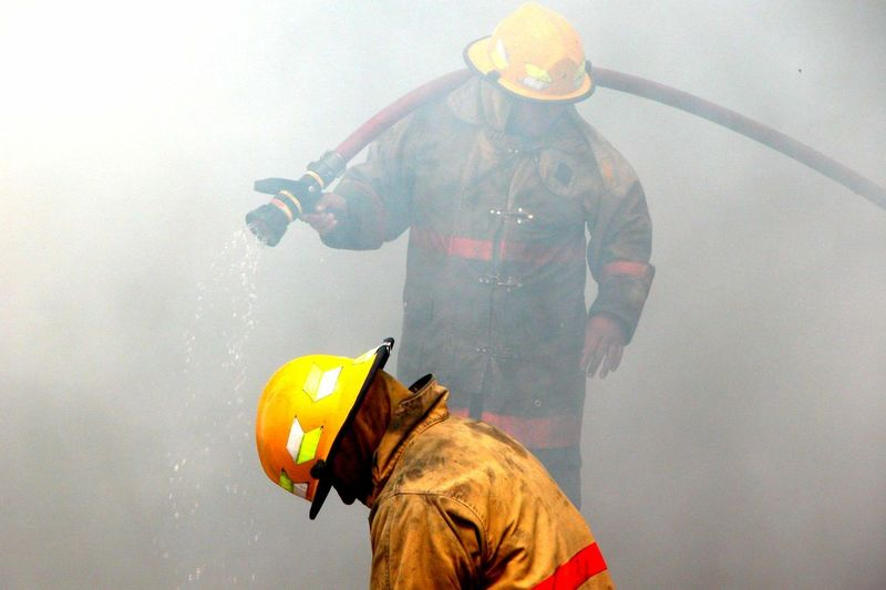 Firefighters with hose in smoke