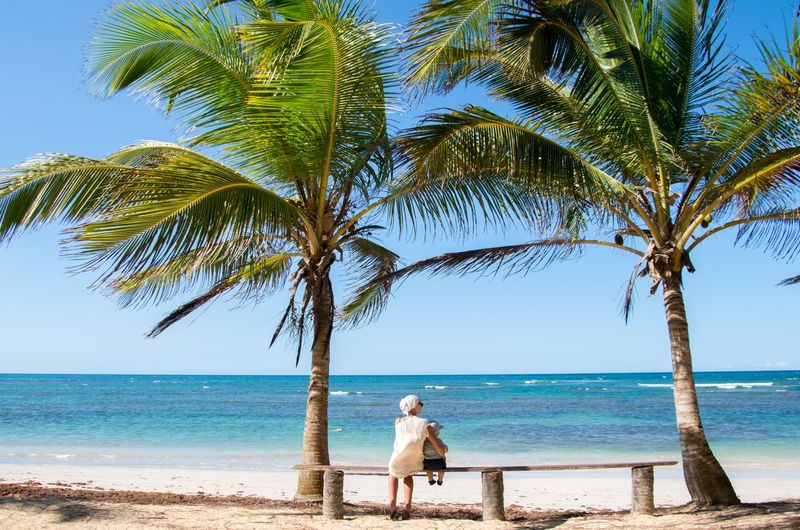 Rear View Of Woman With Son Sitting On Bench At Beach