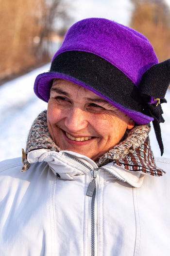 Close-up of thoughtful mature woman wearing purple hat during winter