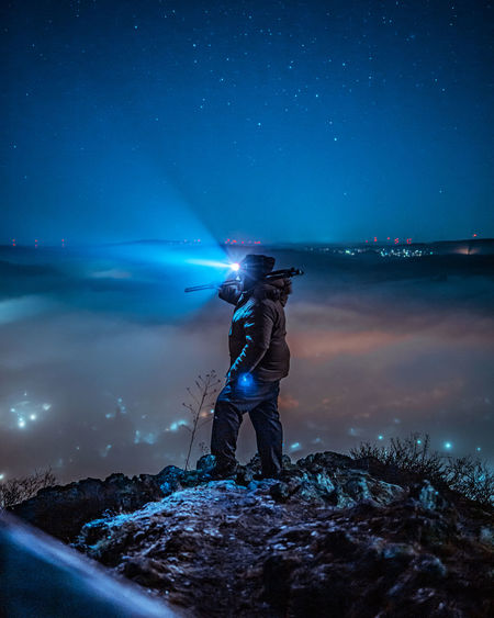 Man standing with illuminated light against sky at night