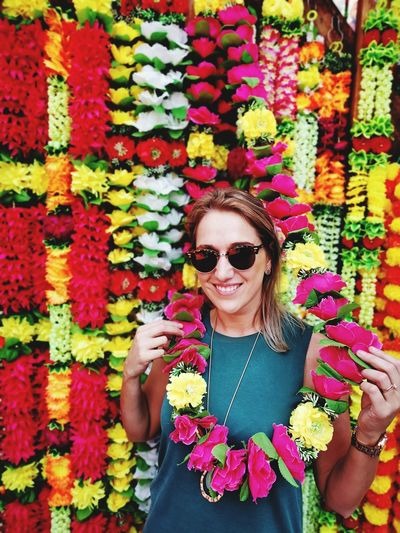 Portrait of smiling woman standing against floral garlands at market