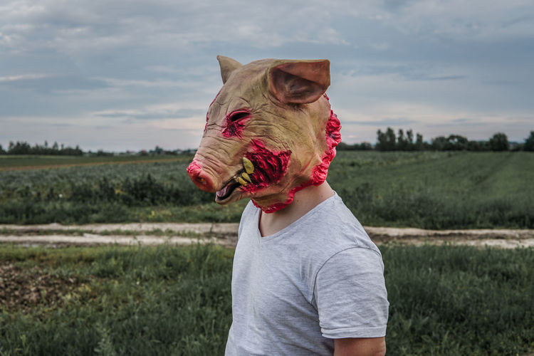 Side view of mid adult man wearing mask standing on land against sky