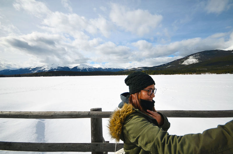 Smiling Woman Standing By Railing Snow Covered Mountain