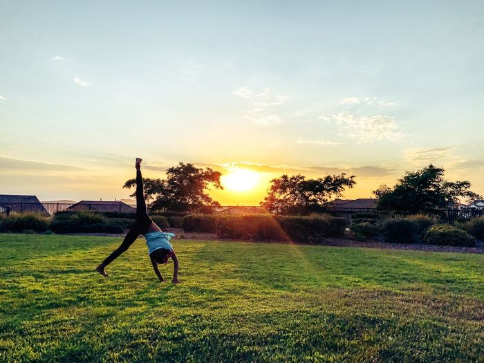 Rear view of girl doing cartwheel on grassy field at park against sky during sunset