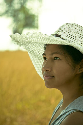 Thoughtful Woman Wearing Straw Hat Looking Up Outdoors