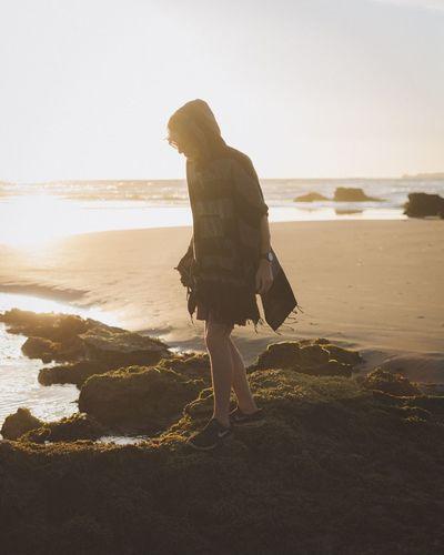 Woman walking on beach against clear sky